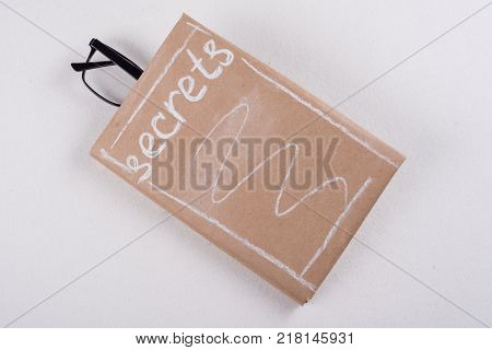 Book is wrapped in old paper and signed secrets, in the book glasses. White background