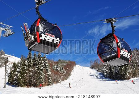 Jasna Slovakia - December 01 2017: Two cabs of the cableway and skiers on the of the mountain Chopok south side on a sunny day in the ski resort of Jasna Low Tatras Slovakia.