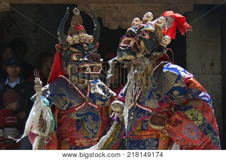 Two Buddhist monks in ancient masks Monsters and bright ritual bathrobes perform the Dance Mask at the feast.