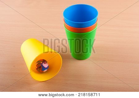 Stack if green red blue plastic colored cups staying on wooden table near laying yellow cup and multicolored small rubber ball inside