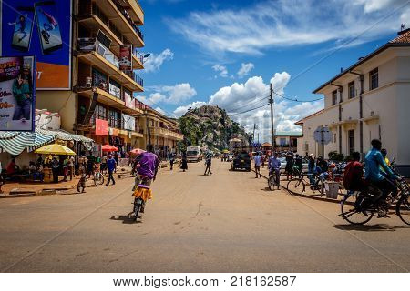 SOROTI, UGANDA - NOVEMBER 04, 2017: Typical street life in Soroti Uganda with its famous rock in the background. Many bicycles and a few cars showing an easy going African town.