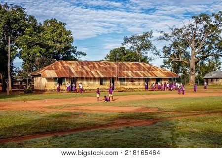 KOLONYI, UGANDA - NOVEMBER 09, 2017: Many students with purple uniform waiting to enter the primary school in Kolonyi near Mbale in Uganda on a beautiful morning in November