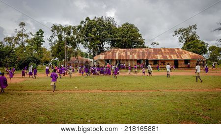 KOLONYI, UGANDA - NOVEMBER 07, 2017: Many students wearing purple uniforms going to the Kolonyi primary school on an early morning. The school is overcrowded with 120 students in one class room
