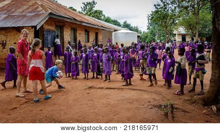 KOLONYI, UGANDA - NOVEMBER 07, 2017: Many students wearing purple uniforms going to the Kolonyi primary school. School is overcrowded with 120 students in one class room. Greeting charity workers