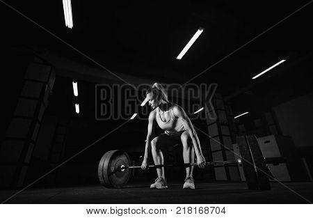 Low angle ahot of a beautiful female crossfit athlete exercising with a barbell copyspace. Young woman training at fitness box doing deadlift complex WOD beauty health power strength