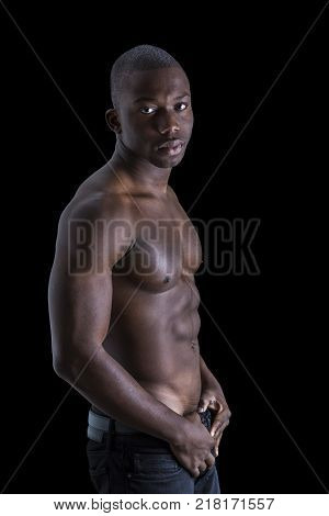Handsome shirtless muscular black young man, looking at camera, on dark background in studio shot