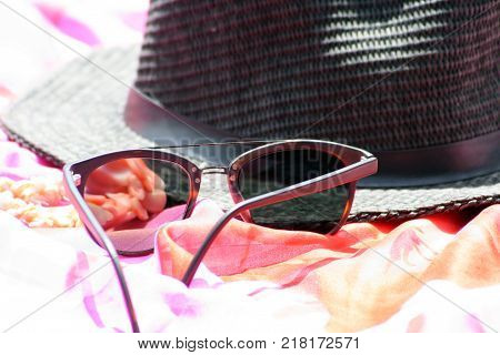 Looking like summer, with sunhat, glasses, coral necklace and sarong.