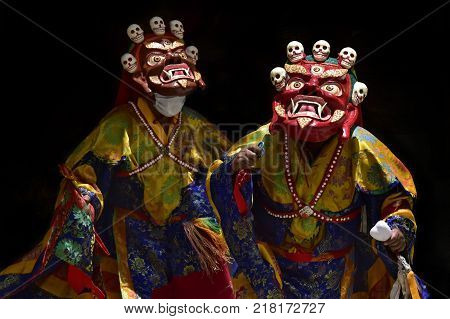 Two red and burgundy ritual costumes of Tibetan Mahakala, ancient wooden masks with bare mouth, long fangs and small human skulls at the top, monastery of Karcha, Zanskar.