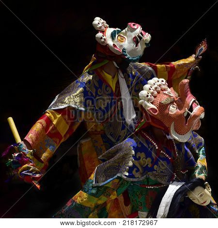 Buddhist monks in ritual national Tibetan clothes perform the Mask Dance depicting human sacrifice.