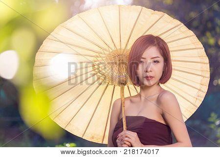 Portrait of asian woman wearing traditional thai holding of yellow umbrella beautiful thai woman in thai costume beautiful asian woman