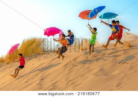 SAMPHUNBOK, TH.  MAY 01, 2016: PARACHUTING OFF SAND DUNES WITH UMBRELLAS: Kids race each other to the top off sand dune and jump off the edge using umbrellas as parachutes to glide them down the dunes.