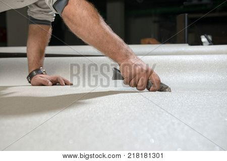 Manual worker cutting vinyl floor with snap off knife.