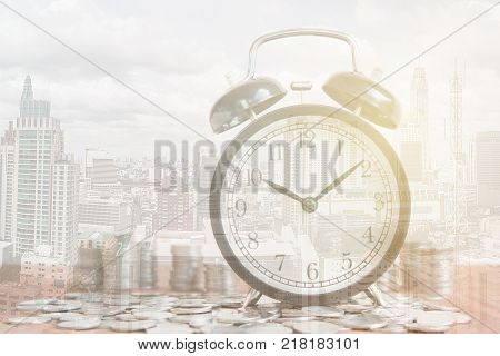 Stack of coins with black fashioned alarm clock for display planning money financial and business accounting concept time is money concept with clock and coins time to work at make money Double exposure