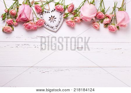 Decorative heart and border from pink roses flowers on white wooden background. Floral still life. Selective focus. View from above.