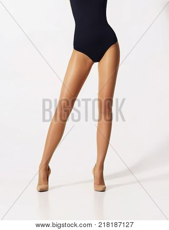 Fit and beautiful legs in sexy pantyhose. Woman in hosiery ovr grey background.