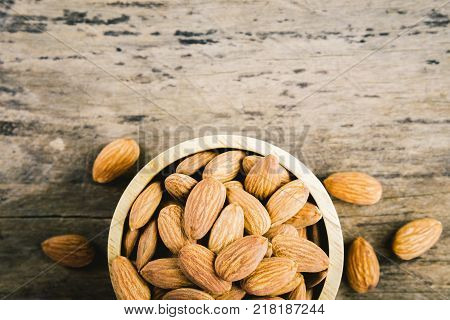 Almonds in brown bowl on textured wooden background top view. Almond vintage tone. Close up almond background.  Close up view of almonds for texture.