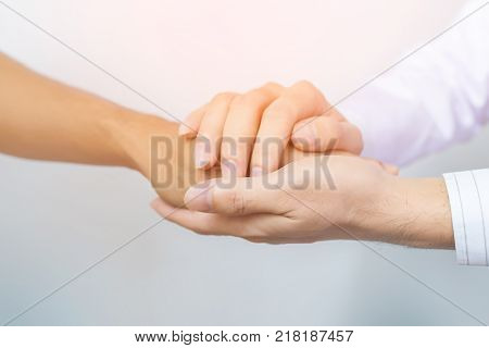 Two people holding hands for comfort. Doctor consoling relatives of patients in hospital concept. comfort Doctor. Doctor hand. Doctor care. Doctor patient