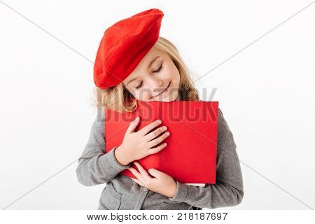 Close up portrait of a loveky little schoolgirl dressed in uniform holding book isolated over white background