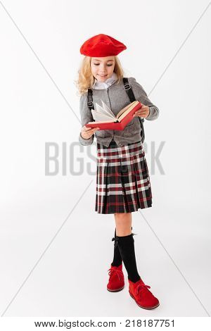 Full length portrait of a happy little schoolgirl dressed in uniform with backpack reading book while standing isolated over white background