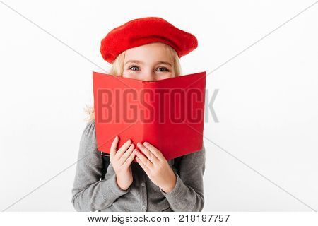 Close up portrait of a little schoolgirl dressed in uniform holding book at her face and looking at camera isolated over white background