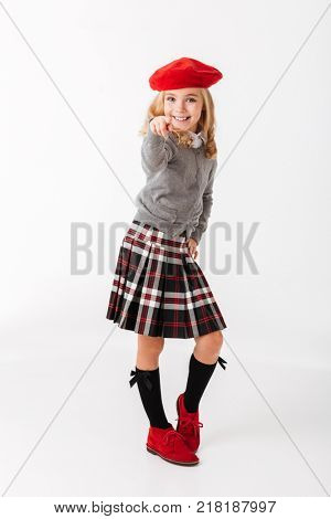 Full length portrait of a smiling little schoolgirl dressed in uniform standing and pointing finger at camera isolated over white background