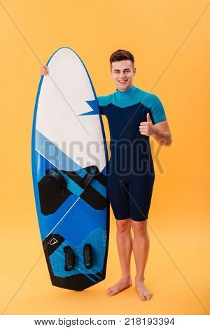 Full length photo of handsome surfer guy in suimsuit holding surfboard while standing and showing thumb up gesture, looking at camera, isolated on yellow background