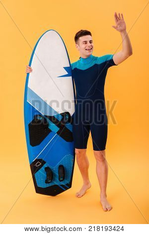 Full length photo of young surfer guy with surfboard showing greeting gesture, isolated over yellow background