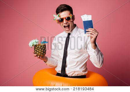 Happy man in sunglasses and official shirt showing cocktail and international passport isolated