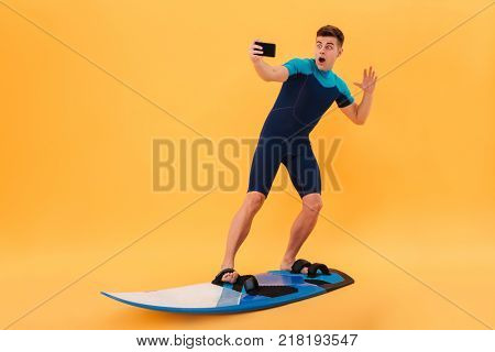 Full length photo of amased surfer guy taking selfie on smartphone while surfing on surfboard, isolated over yellow background