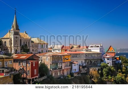 Church above hillside homes in a suburb of Valparaiso, Chile, South America