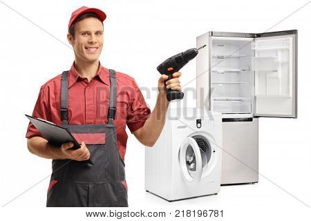 Repairman with a clipboard and a drilling machine in front of a washing machine and a refrigerator isolated on white background