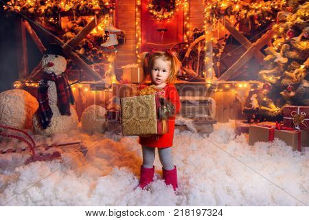 Pretty three year old girl is standing near his house decorated for Christmas and holding a gift. Time for miracles. Merry Christmas and Happy New Year.