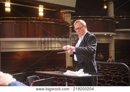 Tyumen, Russia - January 25, 2017: Concert of orchestra of the Tyumen philharmonic hall for photographers. Man conducting an orchestra