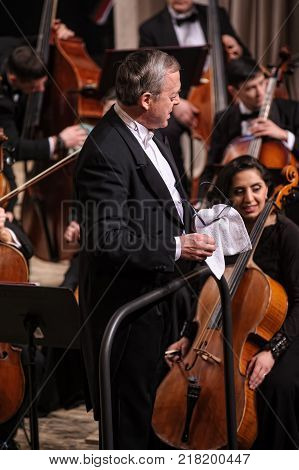 Tyumen, Russia - January 25, 2017: Concert of orchestra of the Tyumen philharmonic hall for photographers. Conductor of symphony orchestra prepers to concert
