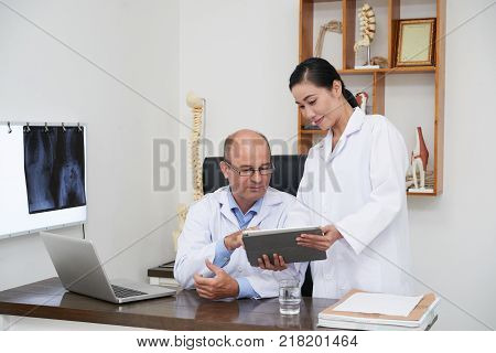 Assistant showing spine x-ray on tablet computer to osteopath