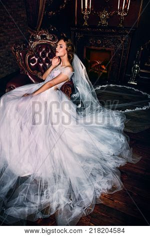 Portrait of a charming bride woman in a beautiful wedding dress. Luxurious vintage apartments.