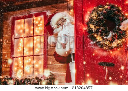 Christmas concept. Portrait of a fairytale Santa Claus peek out from behind the door and leaned his index finger to his lips showing a secret sign. Beautiful house decorated for Christmas.