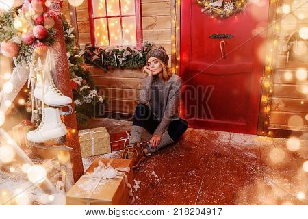 Beautiful young woman is sitting on the porch of a house decorated for Christmas. Time for miracles. Merry Christmas and Happy New Year.