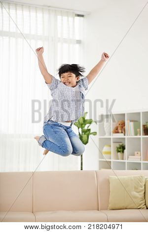 Happy little boy raising amrs when jumping on the sofa at home