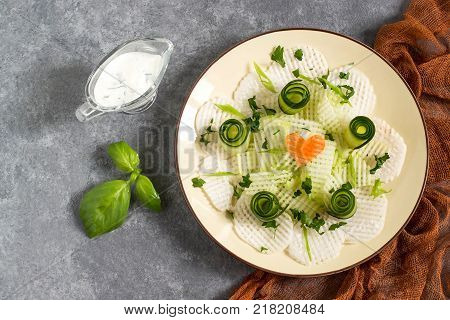 Vitamin salad from daikon with cucumber and herbs. Served with yoghurt sauce. Detox. Vegetarian healthy and diet food. Top view