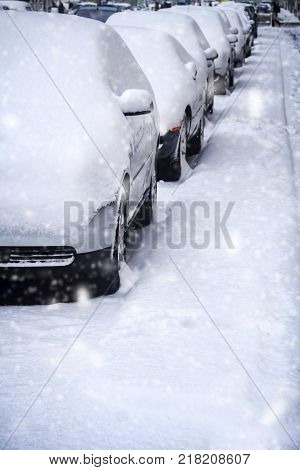 Parked cars in heavy snow on urban street
