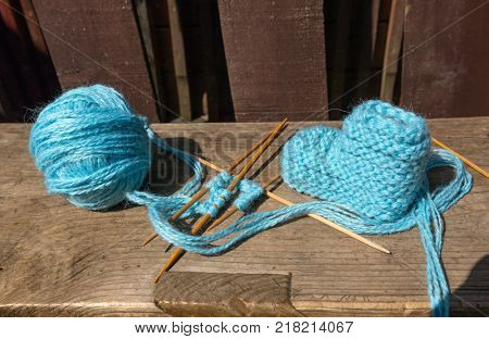 knitting of socks of blue wool, tangle and knitting needles on a wooden table
