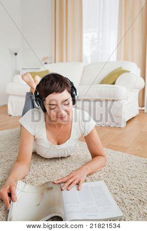 Porträt einer Frau, die eine Magazin und genießen Sie einige Musik lesen