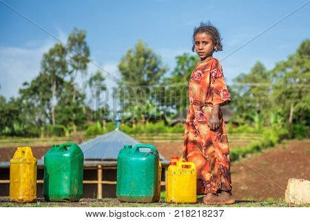 ADDIS ABBABA, ETHIOPIA - MAY 1, 2015 : Young ethiopian girl going for water near Addis Ababa.