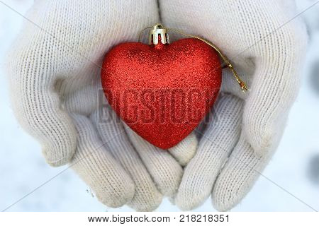 A heart in the arms. White mittens and heart. Heart on the snow. The spirit of Christmas. Christmas traditions. Winter mood. Valentine's day. Love and feelings. Red heart