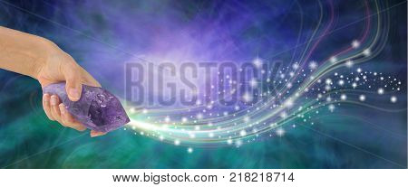 Massive Amethyst Wand with beautiful energy - female hand holding large terminated amethyst quartz wand  shooting out sparkles across a purple and jade energy background with copy space