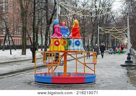 Moscow Russia - February 21 2017: Traditional Dymkovo toy three women in headscarves as art object and Children's carousel at Russian national festival