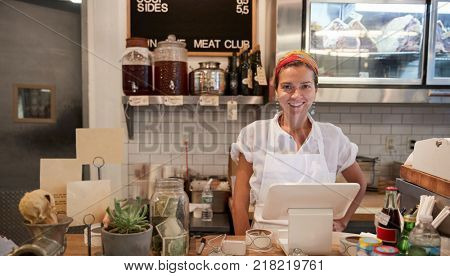 Young woman waiting behind the counter in a butcher's shop