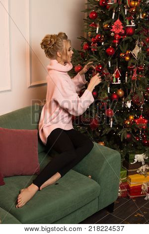 Beautiful blond girl decorate Christmas Tree for celebration New Year night with friends. Beautiful New Year night, happy future Christmas party. Unreal emotion with beautiful interior for Christmas