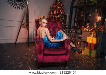 Beautiful sexy woman sit in the red chair. Glamour blond girl in sexy dress and high heel shoes fashion sitting and look sexy. Celebrate New Year in beautiful new dress. Party 2018